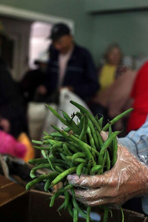 A volunteer prepares to pass out handfuls of green beans at Hosana Celebration Center on Tuesday, August 9, 2011 in San Francisco, Calif.  The food is provided to the center by the San Francisco Food Bank. Photo: Lea Suzuki, The Chronicle