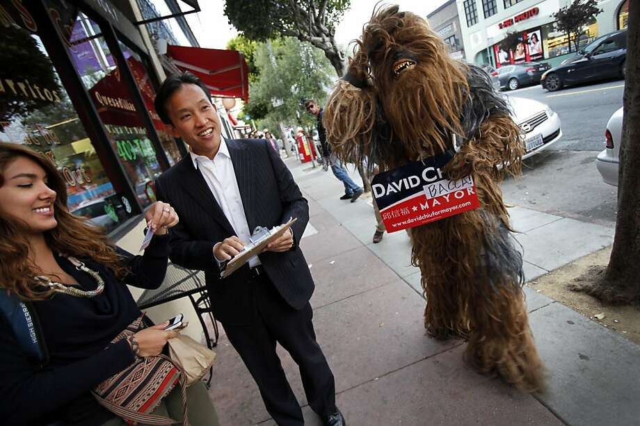 "Mayoral candidate and Board of Supervisors President David Chiu, center, talks with Mahsa Kasiri, left, of San Francisco, while campaigning along Polk St. in San Francisco, Calif., Tuesday.  Chiu's team has a supporter dressed in a full Chewbacca costume from Star Wars with a sign that reads ""Chiubacca."" Photo: Sarah Rice, Special To The Chronicle"