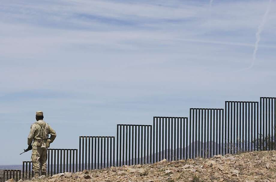 A Mexican soldier patrols along the U.S.-Mexico border wall on the outskirts of Nogales, Mexico, Tuesday, April 1, 2008.  U.S. officials say the Bush administration will bypass more than 30 laws and regulations in an effort to complete 670 miles (1,050 kilometers) of fence along the U.S. border with Mexico by the end of this year. (AP Photo/Guillermo Arias) Ran on: 04-02-2008  Ran on: 04-02-2008  Ran on: 09-11-2008 A Mexican soldier patrols along the U.S.-Mexico border wall on the outskirts of Nogales, Mexico. Photo: Guillermo Arias, AP