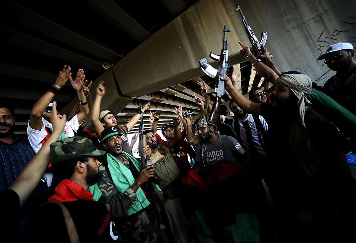 Libyan rebels celebrate as they gain positions against regime forces in the city of Zawiya, some 40 kms west of Tripoli, on August 19, 2011. Libyan rebels claimed to have taken two more key objectives in their advance on Tripoli, including the refinery town of Zawiya, as people scrambled to flee the increasingly isolated capital. AFP PHOTO / FILIPPO MONTEFORTE (Photo credit should read FILIPPO MONTEFORTE/AFP/Getty Images)