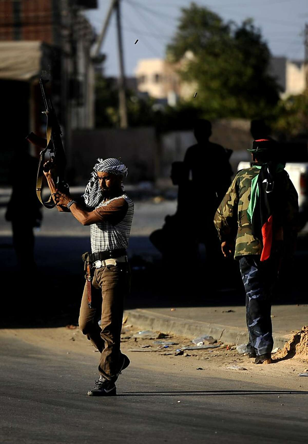 A Libyan rebel fires celebratory shots in the air after gaining positions against regime forces in Zawiya, some 40 kms west of Tripoli, on August 19, 2011. Libyan rebels claimed to have taken two more key objectives in their advance on Tripoli, including the refinery town of Zawiya, as people scrambled to flee the increasingly isolated capital. AFP PHOTO / FILIPPO MONTEFORTE (Photo credit should read FILIPPO MONTEFORTE/AFP/Getty Images)