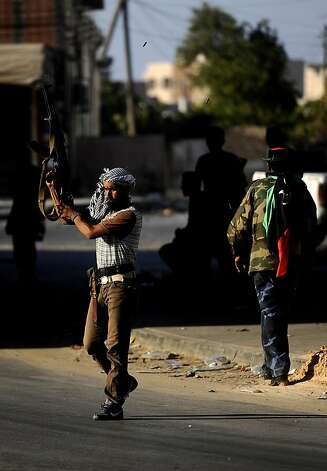 A Libyan rebel fires celebratory shots in the air after gaining positions against regime forces in Zawiya, some 40 kms west of Tripoli, on August 19, 2011. Libyan rebels claimed to have taken two more key objectives in their advance on Tripoli, including the refinery town of Zawiya, as people scrambled to flee the increasingly isolated capital. AFP PHOTO / FILIPPO MONTEFORTE (Photo credit should read FILIPPO MONTEFORTE/AFP/Getty Images) Photo: Filippo Monteforte, AFP/Getty Images