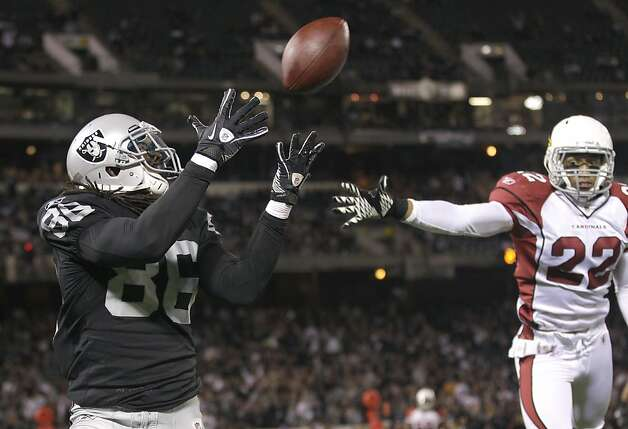FILE - In this photo taken Thursday, Aug. 11, 2011, Oakland Raiders tight end David Ausberry (86) catches a touchdown past Arizona Cardinals safety Matt Ware (22) in the second half of an NFL preseason football game in Oakland, Calif. Transitioning from college to the NFL is hard enough. Doing it at a different position is far more difficult. Ausberry is doing it seamlessly, going from a little-used wide receiver at USC to a promising tight end prospect with the Raiders. (AP Photo/Marcio Jose Sanchez, File0  Ran on: 08-20-2011 David Ausberry  --  all 6-feet-4, 247 pounds of him  --  gets behind Arizona's Matt Ware for a touchdown reception. Photo: Marcio Jose Sanchez, AP