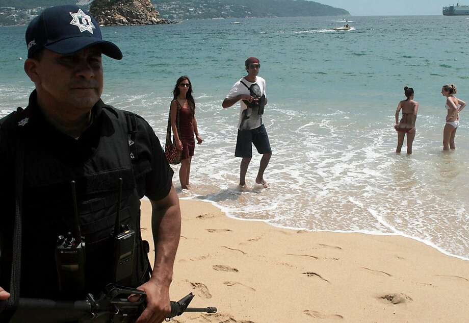 Tourists enjoy the beach next to a policeman on patrol in the resort city of Acapulco, Guerrero state, Mexico on March 16, 2010. More than 30 people have died in recent attacks in the city. Drug-related crime has left more than 15,000 dead in the past three years in Mexico, despite a nationwide clampdown on the growing violence involving the deployment of some 50,000 government troops. AFP PHOTO / Pedro Pardo (Photo credit should read Pedro PARDO/AFP/Getty Images)  Ran on: 03-19-2010 Tourists enjoy the beach next to a police officer on patrol in Acapulco, Mexico. The country's push to draw tourists, the third-biggest source of dollars, is hampered by violence connected to drug trafficking. Photo: Pedro Pardo, AFP/Getty Images