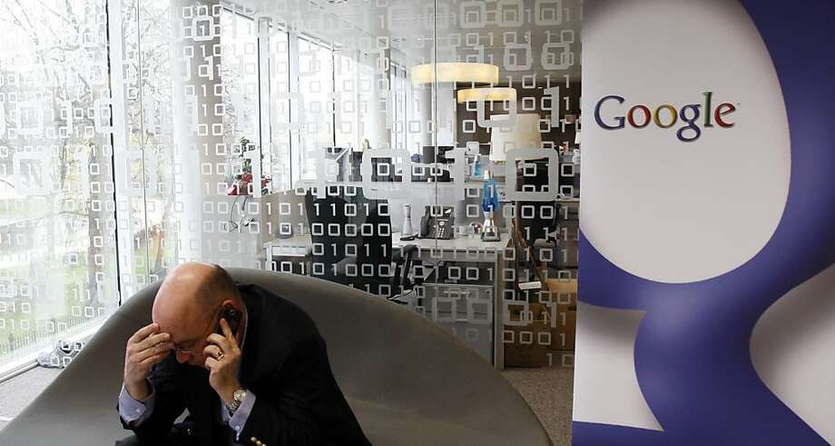 Head of Communications for Google Europe, William Echikson, left, speaks on his cell phone at the Google headquarters in Brussels, Tuesday March 23, 2010. Google Inc. has won a key European Court ruling that says it did not violate luxury manufacturers' trademarks by allowing counterfeiters buy brand names as advertising key words that link to online stores offering fake goods. In a Tuesday ruling, the European Court of Justice says Louis Vuitton and other French luxury companies should turn to the French courts to seek compensation for possible damage from the misuse of their trademark. (AP Photo/Virginia Mayo)  Ran on: 03-24-2010 William Echikson, head of communications for Google Europe, speaks on his cell phone at company headquarters in Brussels after the ruling. Ran on: 03-24-2010 William Echikson, head of communications for Google Europe, speaks on his cell phone at company headquarters in Brussels after the ruling.  Ran on: 07-19-2011 William Echikson, head of communications for Google Europe, says a deal has been reached to bring Belgian papers as &quo;quickly as possible.&quo; Photo: Virginia Mayo, AP