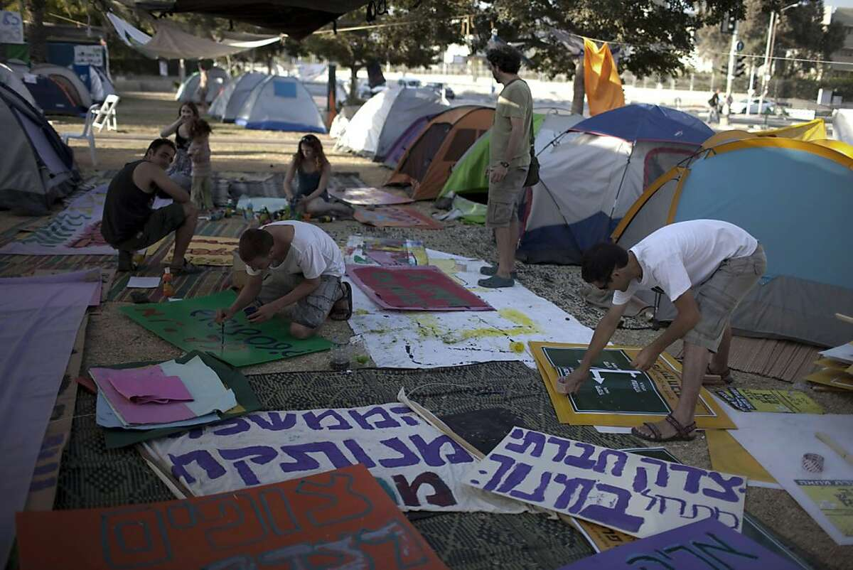 Israeli protestors prepare anti-government posters at their protest tent camp, before the evening's demonstration in the southern Israeli city of Beersheva on August 13, 2011, to protest against rising housing prices and social inequalities in the Jewishstate. Thousands of Israelis are expected to demonstrate across the country to protest against the high cost of living.