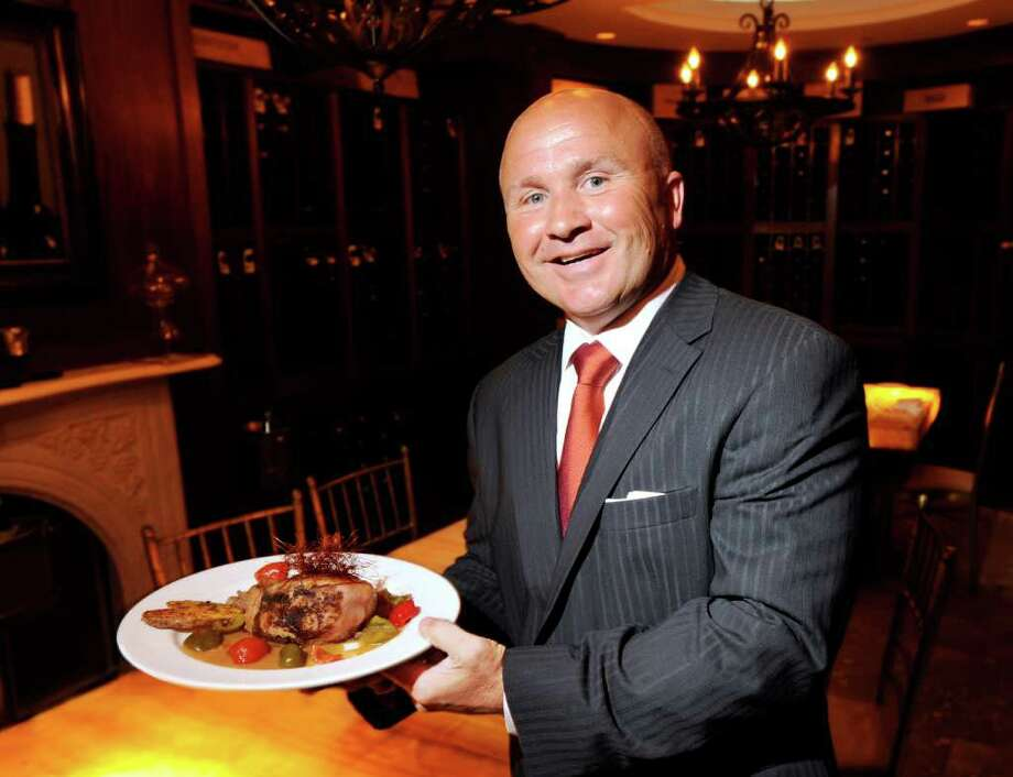 Anthony Capasso, manager of Gabriele's Italian Steakhouse, poses with a Berkshire pork chop at the Church Street restaurant in June. In a conditional arrangement, the Planning and Zoning Commission agreed Tuesday to allow the restaurant to open a second floor banquet hall. Photo: Bob Luckey, ST / Greenwich Time