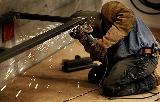 A worker grinds down a weld on the frame of a metal office bench in one of the football team office Tuesday, August.16, 2011. Construction workers continue to complete Cal's new Student Athlete High Performance Center that's scheduled to open Sept 1st. The project spans the west side of Memorial Stadium and will house 13 different sport teams including an Olympic Center at a cost of $150 Million primarily from private money. Photo: Lance Iversen, The Chronicle