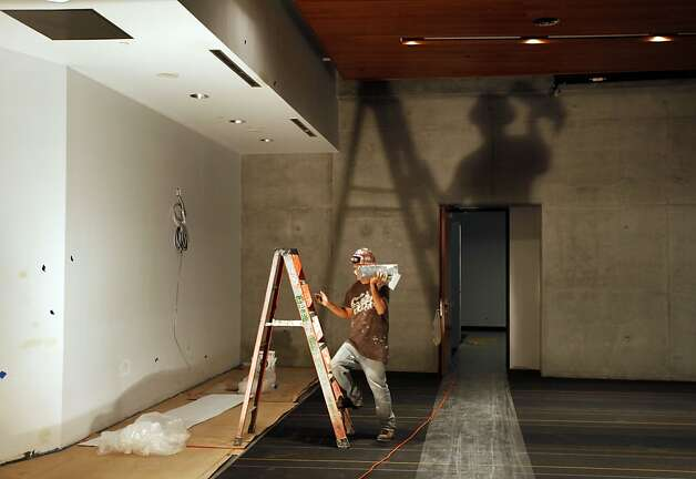 A dry wall worker cast a big shadow in the new cafeteria. Construction workers continue to complete Cal's new Student Athlete High Performance Center that's scheduled to open Sept 1st. The project spans the west side of Memorial Stadium and will house 13 different sport teams including an Olympic Center at a cost of $150 Million primarily from private money. Tuesday, Aug 16, 2011. Photo: Lance Iversen, The Chronicle
