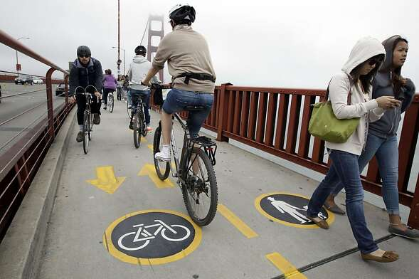 Bicyclists and pedestrians walk or ride on the Golden Gate Bridge in San Francisco, Wednesday, Aug. 3, 2011. Golden Gate Bridge officials have skirted a smashup over proposed bicycle speed limits by putting up new signs and creating separate lanes across the famous span to keep the peace between pedestrians and cyclists forced to share the bridge's one remaining open sidewalk. Beginning this week, the new signs on lamp posts and yellow road striping split the east sidewalk into one lane for pedestrians and another for bikers. (AP Photo/Paul Sakuma)