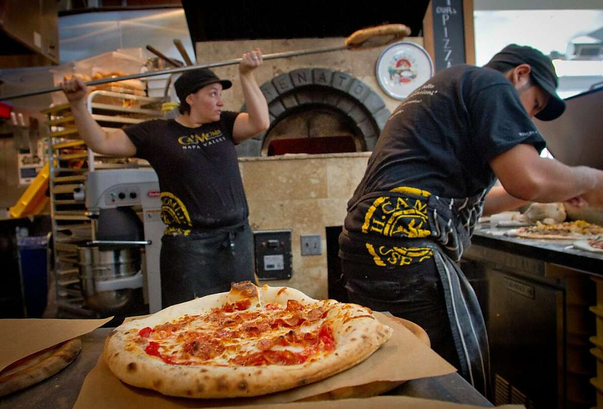 Freddie Rodriquez makes pizzas as Sylvana Bertolini pulls a pizza from the oven at Ca'Momi at the Oxbow Market in Napa, Calif., on August 12th, 2011.