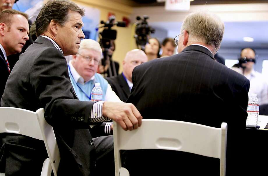 Republican presidential candidate, Texas Gov. Rick Perry, left, talks with Resonetics President Clifford Gabay, right, and others, during a round table with local businessmen in Nashua, N.H., Wednesday,Aug.  17, 2011. (AP Photo/Cheryl Senter) Photo: Cheryl Senter, AP