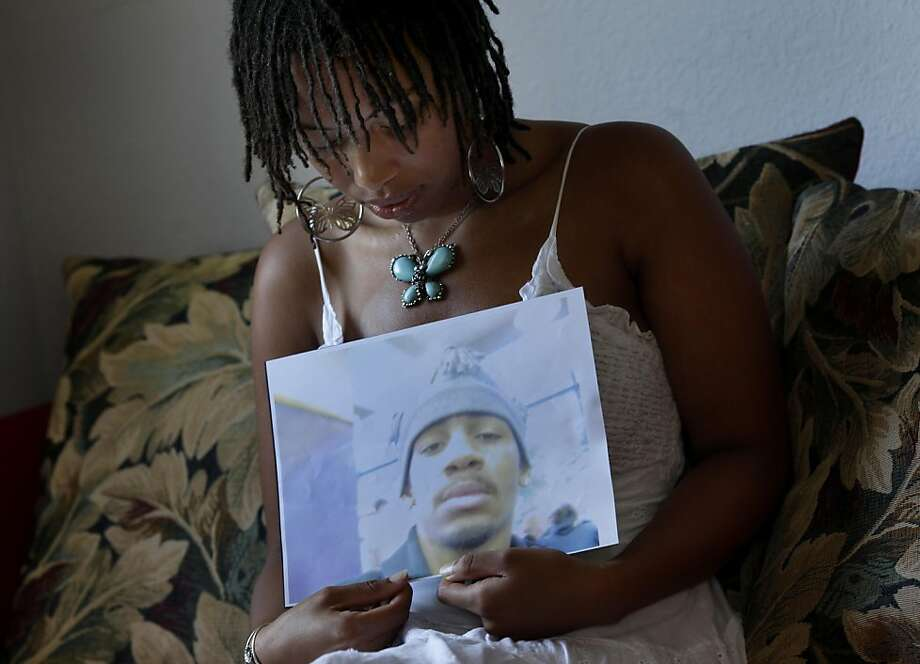 Oya Sherrills held a photo of her dead brother Terrell in her home in El Sobrante. Oya Sherrills, 23, lost her brother to gang violence in 2004 but she still supports SB9, which would let juvenile offenders appeal their life without parole sentences. Photo: Brant Ward, The Chronicle