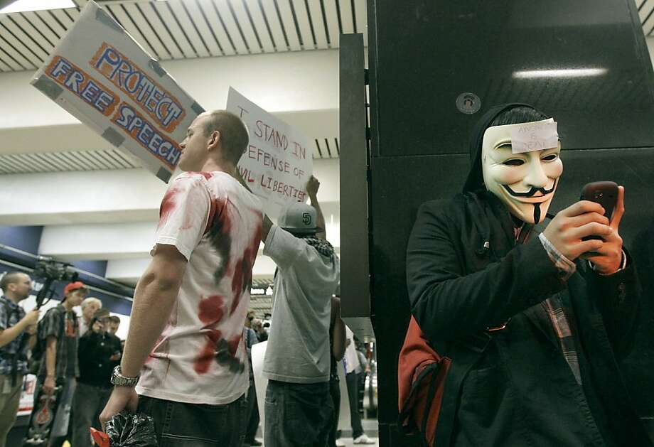 An unidentified protester uses his cell phone during a protest at the Civic Center BART station in San Francisco, Monday, Aug. 15, 2011. Cellphone service was operating as protesters gathered at the San Francisco subway station during rush-hour several days after transit officials shut wireless service to head off another demonstration. (AP Photo/Jeff Chiu) Photo: Jeff Chiu, AP