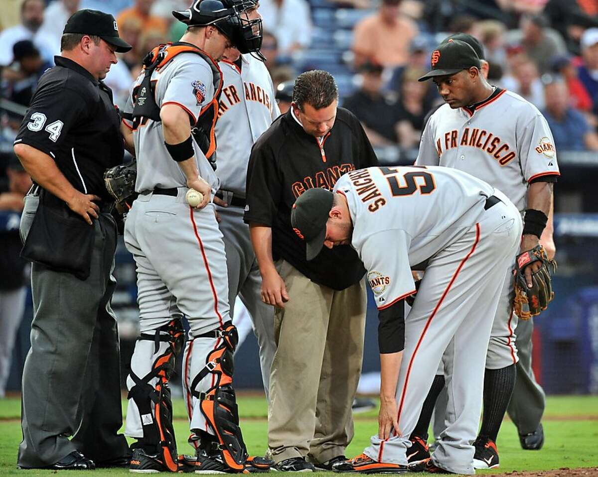 San Francisco Giants starting pitcher Jonathan Sanchez (57) is surrounded by teammates and staff after he hurt himself in the third inning against the Atlanta Braves at Turner Field in Atlanta, Georgia, on Tuesday, August 16, 2011. (Hyosub Shin/Atlanta Journal-Constitution/MCT) Ran on: 08-17-2011 Jonathan Sanchez is surrounded after he sprained his ankle in the third inning. Ran on: 08-17-2011 Jonathan Sanchez is surrounded after he sprained his ankle in the third inning.