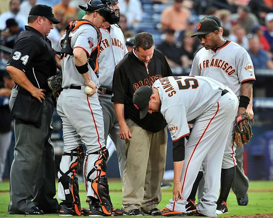 San Francisco Giants starting pitcher Jonathan Sanchez (57) is surrounded by teammates and staff after he hurt himself in the third inning against the Atlanta Braves at Turner Field in Atlanta, Georgia, on Tuesday, August 16, 2011. (Hyosub Shin/Atlanta Journal-Constitution/MCT) Ran on: 08-17-2011 Jonathan Sanchez is surrounded after he sprained his ankle in the third inning. Ran on: 08-17-2011 Jonathan Sanchez is surrounded after he sprained his ankle in the third inning. Photo: Hyosub Shin, MCT