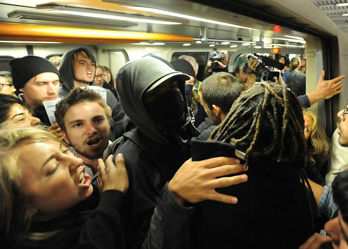 Some protesters cram into a train at the Civic Center Platform while BART employees tried to keep them off the train on July 11, 2011. The protest was held where Charles Hill was killed by BART police on July 2, 2011.