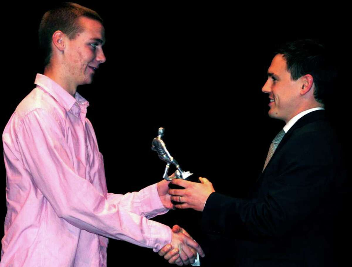 SPECTRUM/Green Wave boys' soccer coach James Tong, right, presents his team's Most Valuable Player trophy to Kevin McSherry during the New Milford High School fall sports awards ceremony. Nov. 28, 2011