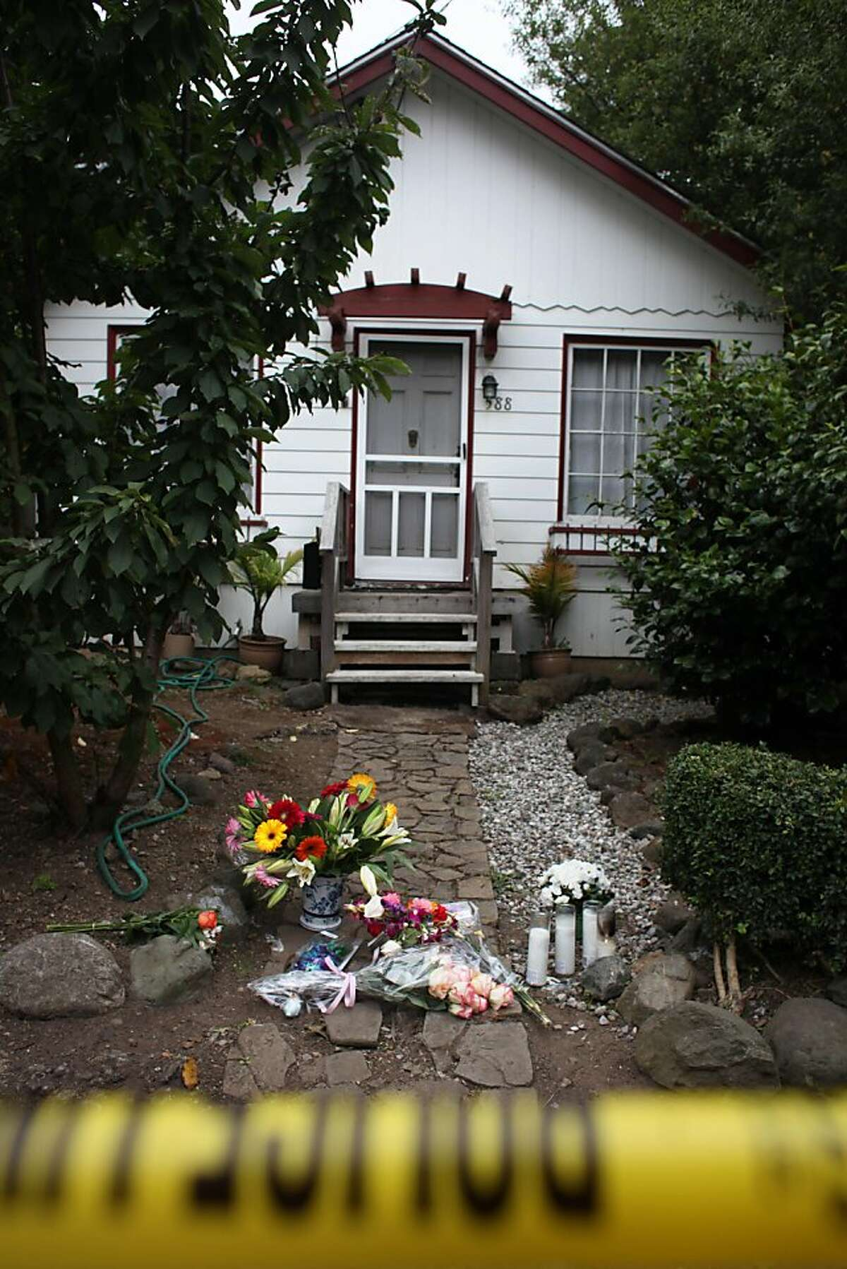 Flowers and candles are seen in the walkway leading up to the home where Darla Napora, 32, was mauled and killed by a family pit bull Thursday on Friday, August 12, 2011 in Pacifica, Calif.