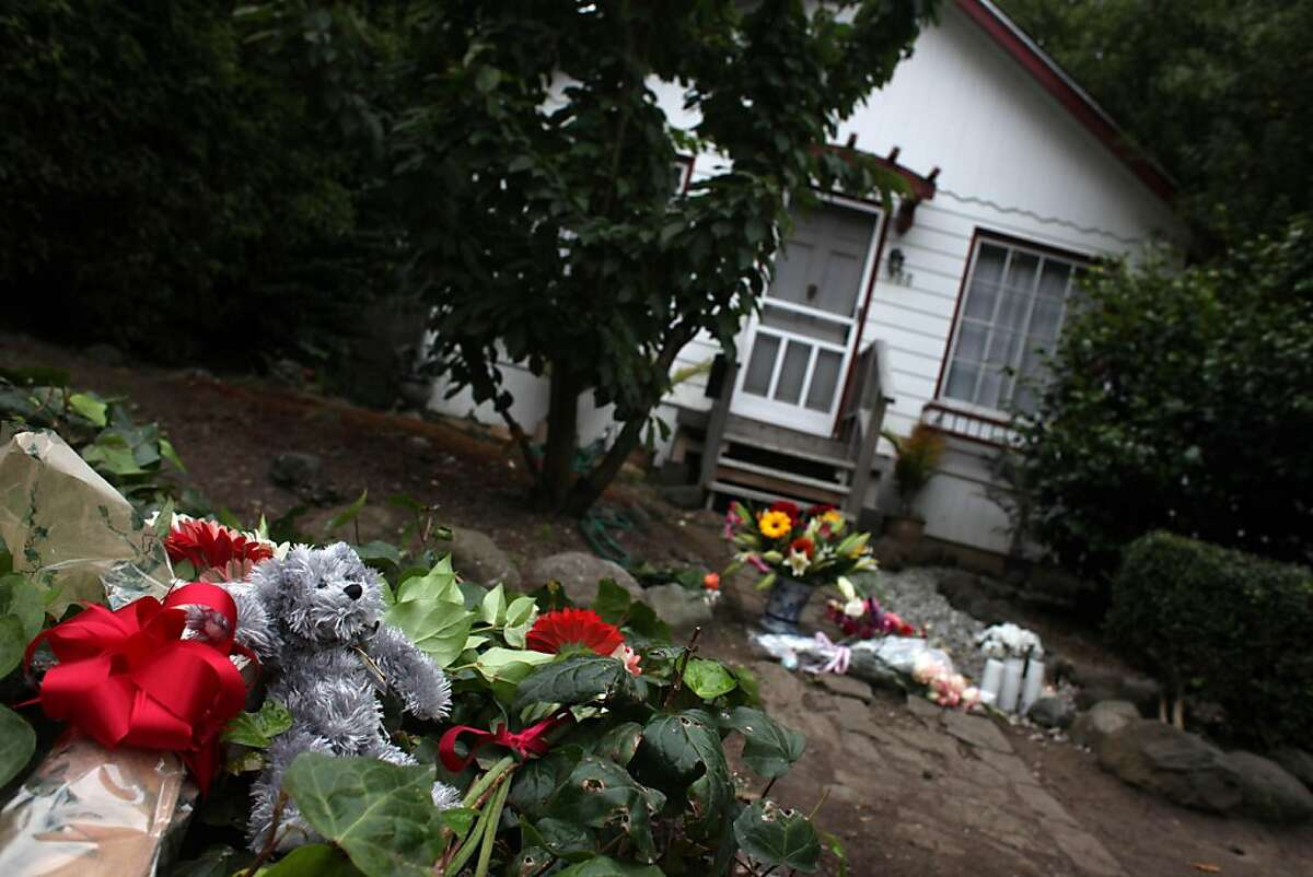 A stuffed animal, flowers and candles are seen in the walkway leading up to the home where Darla Napora, 32, was mauled and killed by a family pit bull Thursday on Friday, August 12, 2011 in Pacifica, Calif.