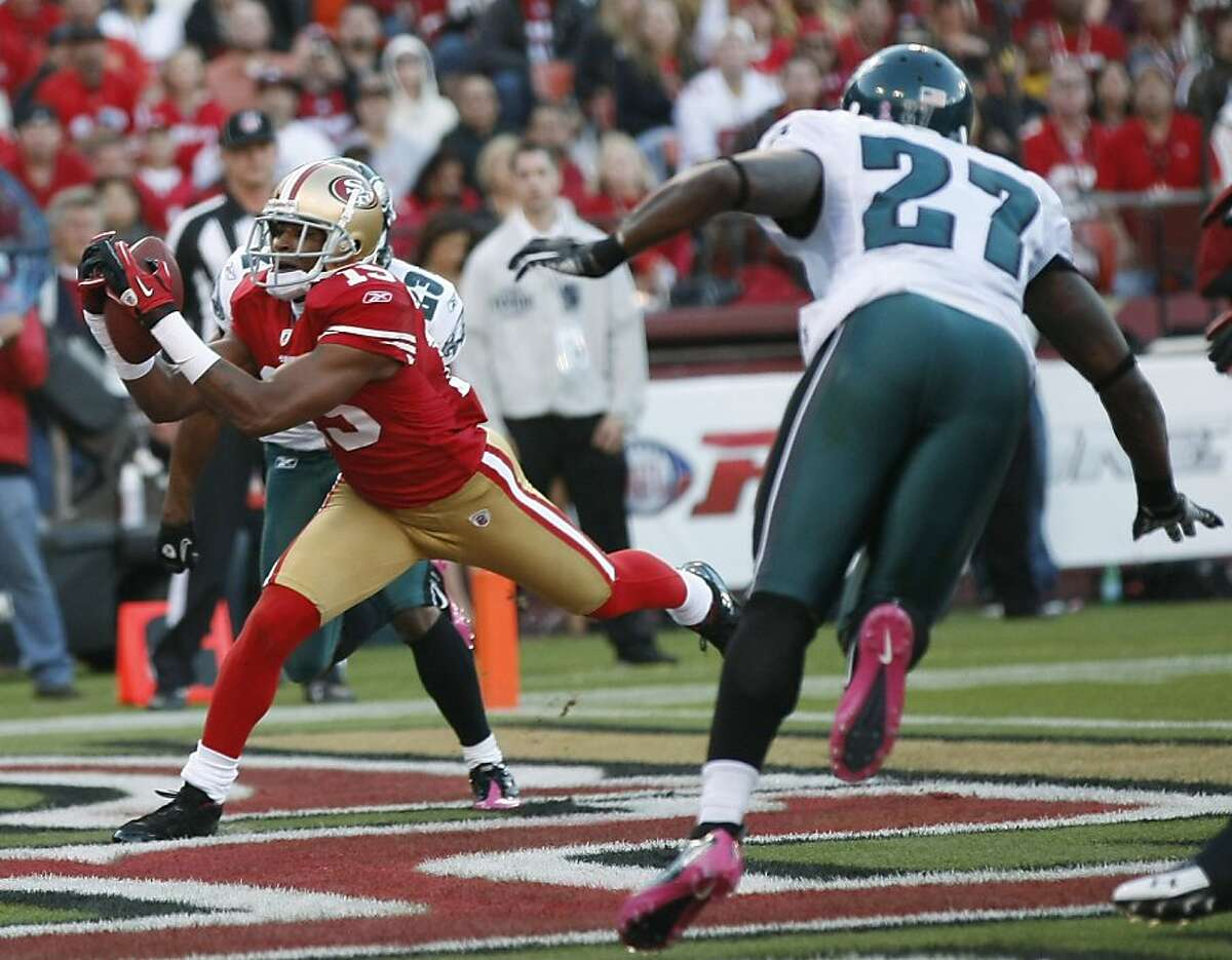 San Francisco 49ers wide receiver Michael Crabtree, left, scores a touchdown on a seven-yard reception from quarterback Alex Smith as Philadelphia Eagles safety Quintin Mikell, right, looks on during the first quarter of their NFL football game in San Francisco, Sunday, Oct. 10, 2010. (AP Photo/Marcio Jose Sanchez) Ran on: 10-15-2010 Michael Crabtree scored a touchdown against the Eagles on Sunday, part of his first 100-yard game as a pro.
