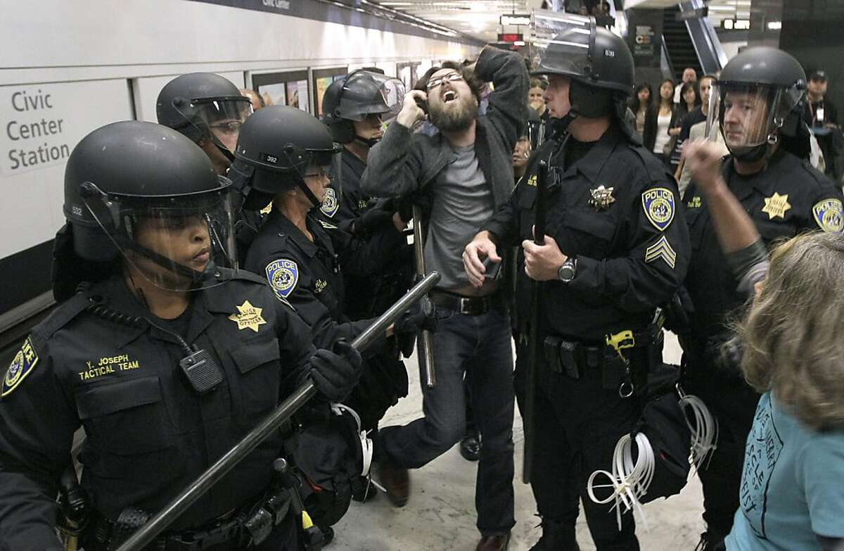 BART police officers push back a protester at the Civic Center station in San Francisco, Monday, Aug. 15, 2011. Cellphone service was operating as protesters gathered at a San Francisco subway station during rush-hour several days after transit officialsshut wireless service to head off another demonstration.
