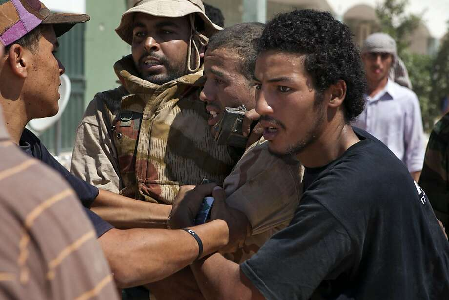 Libyan rebels protect a captured enemy sniper from retaliation of other rebel fighters near Zawiya in western Libya, Saturday, Aug. 13, 2011. After some moment of tension the prisoner, whose name has not been released yet, was put in a car an drove towards Zintan. Libyan rebels fought their way into the strategic city of Zawiya west of Tripoli on Saturday in their most significant advance in months, battling snipers on rooftops and heavy shelling from Moammar Gadhafi's forces holding the city. (AP Photo/Giulio Petrocco) Photo: Giulio Petrocco, AP