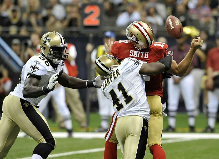 San Francisco 49ers quarterback Alex Smith (11) is hit by New Orleans Saints safety Roman Harper (41) as defensive end Alex Brown (96) pursues during the first quarter of an NFL preseason football game at the Louisiana Superdome in New Orleans, Friday, Aug. 12, 2011. (AP Photo/Bill Feig)  Ran on: 08-13-2011 Alex Smith, hit here by Saints safety Roman Harper, was under constant pressure and finished 2-for-7 for 10 yards. Ran on: 08-13-2011 Alex Smith, hit here by Saints safety Roman Harper, was under constant pressure and finished 2-for-7 for 10 yards. Ran on: 08-13-2011 Alex Smith, hit here by Saints safety Roman Harper, was under constant pressure and finished 2-for-7 for 10 yards. Photo: Bill Feig, AP