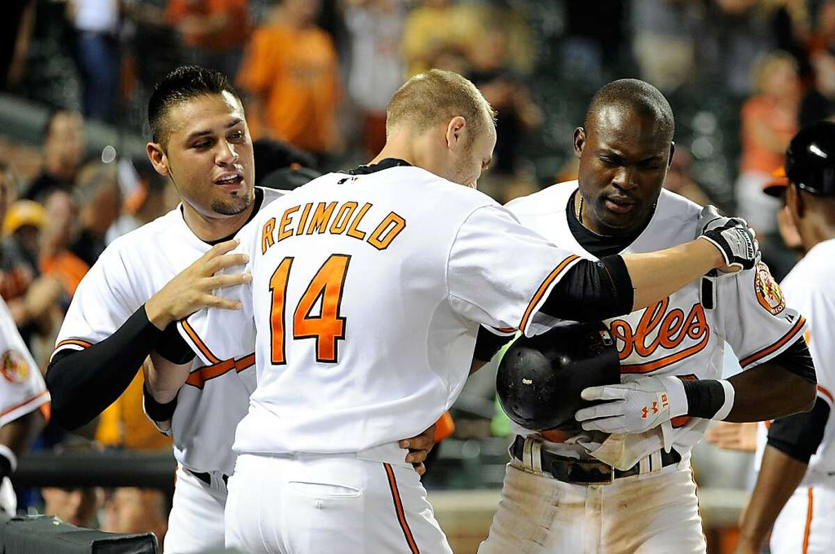 BALTIMORE, MD - AUGUST 10: Nolan Reimold #14 of the Baltimore Orioles celebrates with Felix Pie #18 and Robert Andino #11 after hitting the game winning home run in the tenth inning against the Chicago White Sox at Oriole Park at Camden Yards on August 10, 2011 in Baltimore, Maryland. The Orioles won the game 6-4.