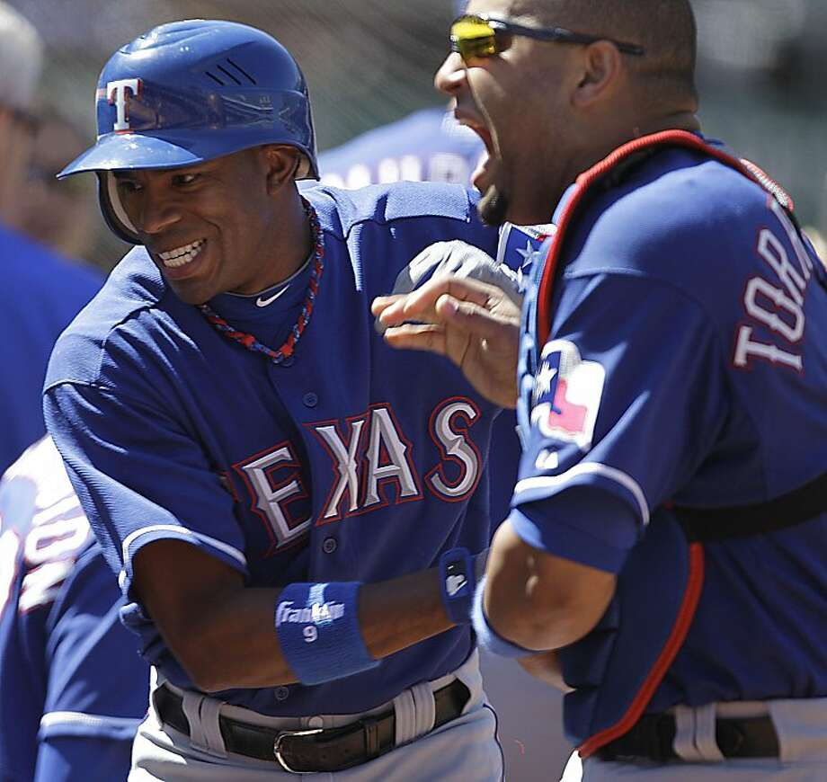 Texas Rangers' Endy Chavez, left, celebrates after scoring against the Oakland Athletics with teammate Yorvit Torrealba during the eighth inning of a baseball game, Saturday, Aug. 13, 2011, in Oakland, Calif. Chavez scored on a double by Elvis Andrus. Photo: Ben Margot, AP