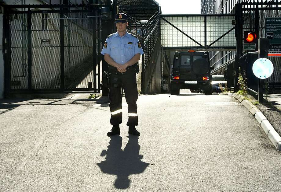 A police officer guards the entrance as the convoi (R) carrying Anders Behring Berivik for questioning passes through the gates at the Police headquarters in Oslo on July 29, 2011. Breivik has confessed to the attack on government buildings and massacre on the youth camp of the Norwegian Labour Party.  At least 76 were killed in last Friday's attacks in Norway, a bombing in central Oslo and a series of shootings on an island just outside the capital, and the figure could rise, a senior police officer said. Police had also found explosives on the island of Utoeya, where a gunman opened fire on young people at a summer camp organised by the ruling Labour Party, Sveinung Sponheim, acting commissioner for Oslo police, told reporters. AFP PHOTO / ODD ANDERSEN (Photo credit should read ODD ANDERSEN/AFP/Getty Images) Photo: Odd Andersen, AFP/Getty Images