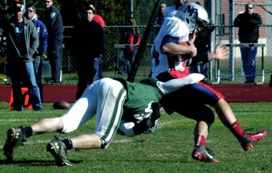 SPECTRUM/Christian Davies of the Green Wave goes low to track down a Rebel ballcarrier on Thanksgiving Day as the New Milford High School football team outlasts visiting New Fairfield, 31-28, to capture the Candlewood Cup. Nov. 24, 2011 Photo: Norm Cummings
