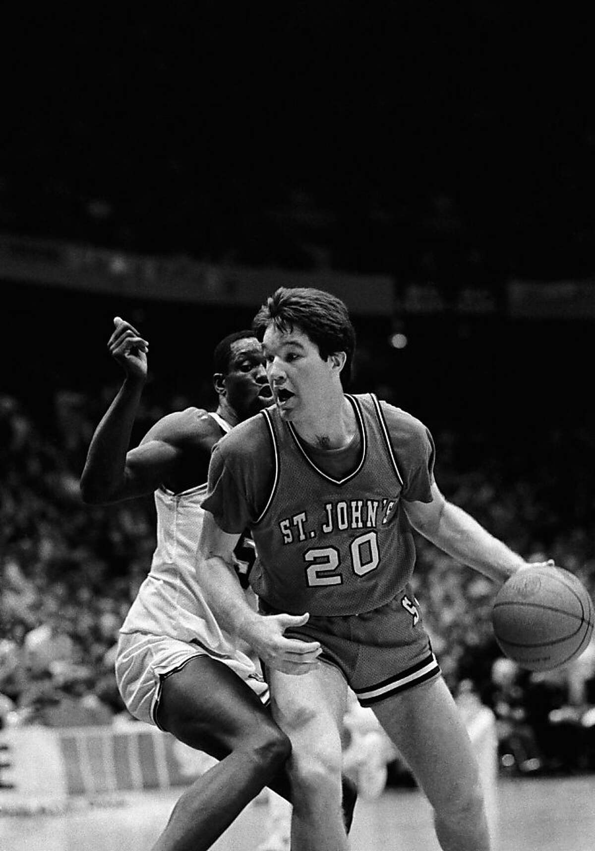 St. John's Chris Mullin drives to the basket around Villanova's Ed Pinckney in the second half of play in Philadelphia on Saturday, Feb.9, 1985. Mullin scored 12 of his 21 points in the final 6:14 of the game as top-ranked St. John's rallied to beat Villanova 70-68.(AP Photo)