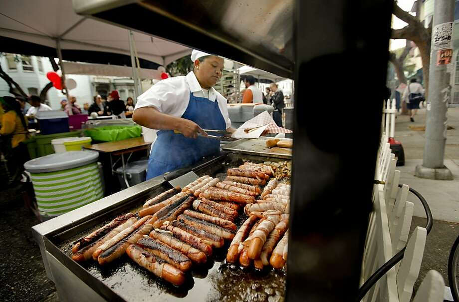 Lucero Munoz, owner of Lucero's Hot Dogs, grills bacon-wrapped dogs at the San Francisco Street Food Festival in the Mission District on Saturday. Photo: Michael Macor, The Chronicle