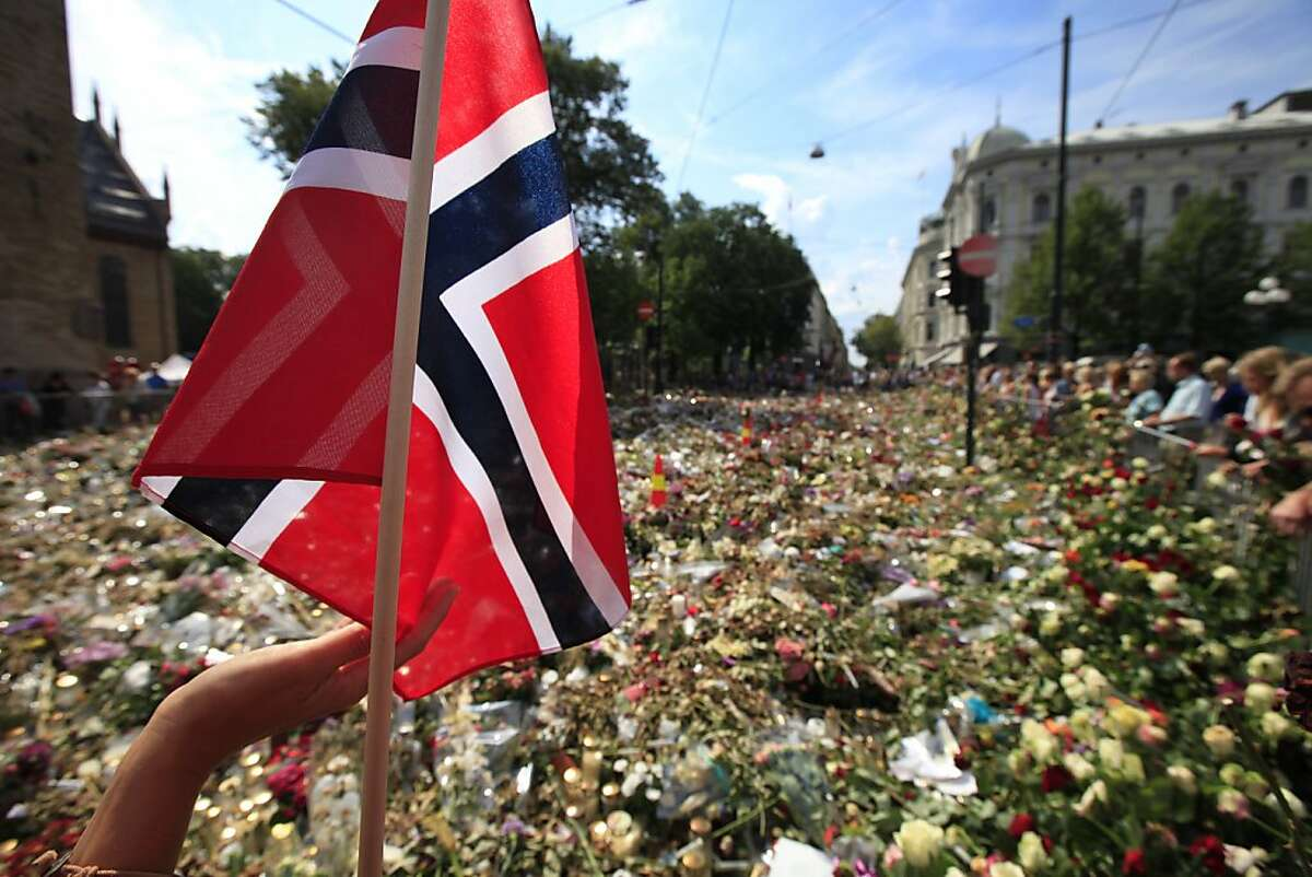 A woman touches a Norwegian flag as people gather around thousands of flowers and tributes laid outside the Oslo Cathedral in Oslo, in memory of the victims of July 22 bomb attack and shooting rampage, Monday, Aug. 1, 2011. Anders Behring Breivik, the 32-year-old Norwegian extremist, has confessed to setting off a car bomb that killed eight people in downtown Oslo and then gunning down scores of youth from the left-leaning Labor Party at their annual retreat on an island northwest of the capital. Sixty-nine of them died