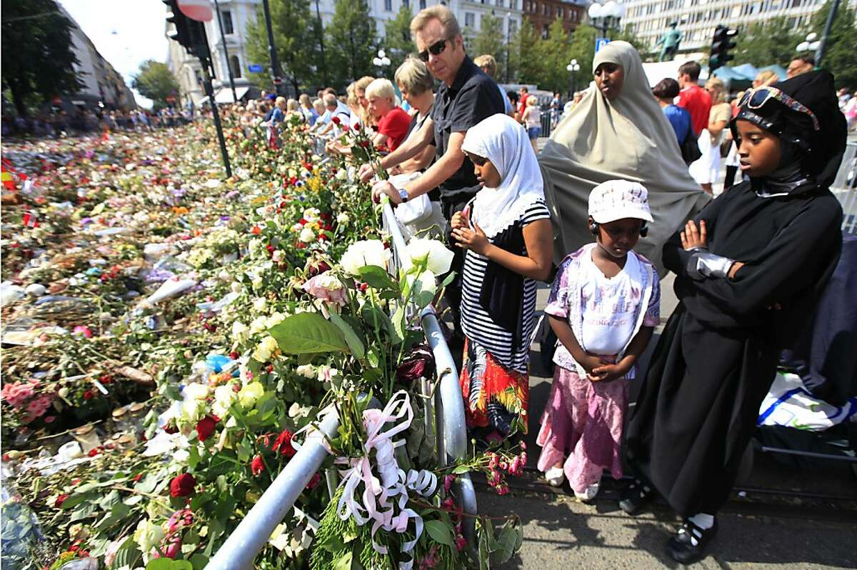 People gather around thousands of flowers and tributes laid outside the Oslo Cathedral in Oslo, in memory of the victims of July 22 bomb attack and shooting rampage, Monday, Aug. 1, 2011. Anders Behring Breivik, the 32-year-old Norwegian extremist, has confessed to setting off a car bomb that killed eight people in downtown Oslo and then gunning down scores of youth from the left-leaning Labor Party at their annual retreat on an island northwest of the capital. (AP Photo/Lefteris Pitarakis)