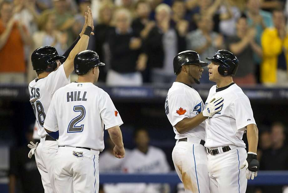 Toronto Blue Jays' Brett Lawrie, right, celebrates his grand slam with teammates, from left, Colby Rasmus, Aaron Hill and Edwin Encarnacion during the sixth inning of a baseball game against the Oakland Athletics in Toronto on Wednesday, Aug. 10, 2011. (AP Photo/The Canadian Press, Chris Young) Photo: Chris Young, AP