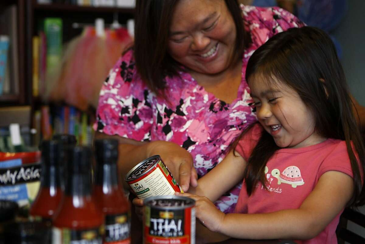 Mimi Jiggins helps her five-year-old daughter Charlotte sound out the words on a can of food she received through House Party in San Francisco Calif., on August 2, 2011.