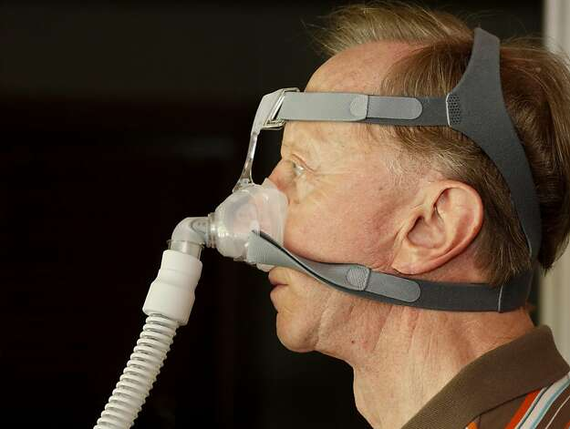 Les Besser demonstrates how the breathing mask of the CPAP machine attaches to his head.  Besser, 75, of Los Altos, Calif., suffers from sleep apnea. He says sleeping on your side is the best position but it takes time to get used to sleeping with the device.  He runs a sleep apnea support group and uses a CPAP machine to get through the night. Photo: Brant Ward, The Chronicle