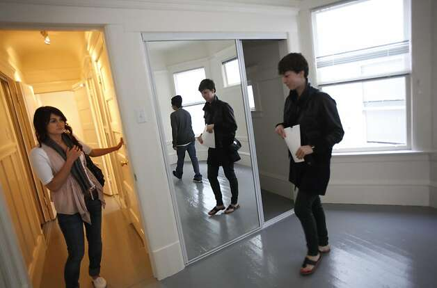 Elise Young, left, and Estevan Padilla, center, both of San Francisco, and Katy Cody, right, of Palo Alto, attend an open house in San Francisco, Calif., August 5, 2011.  Demand is up for apartments in the city, with this studio in the Lower Haight going for $1395. Photo: Sarah Rice, Special To The Chronicle