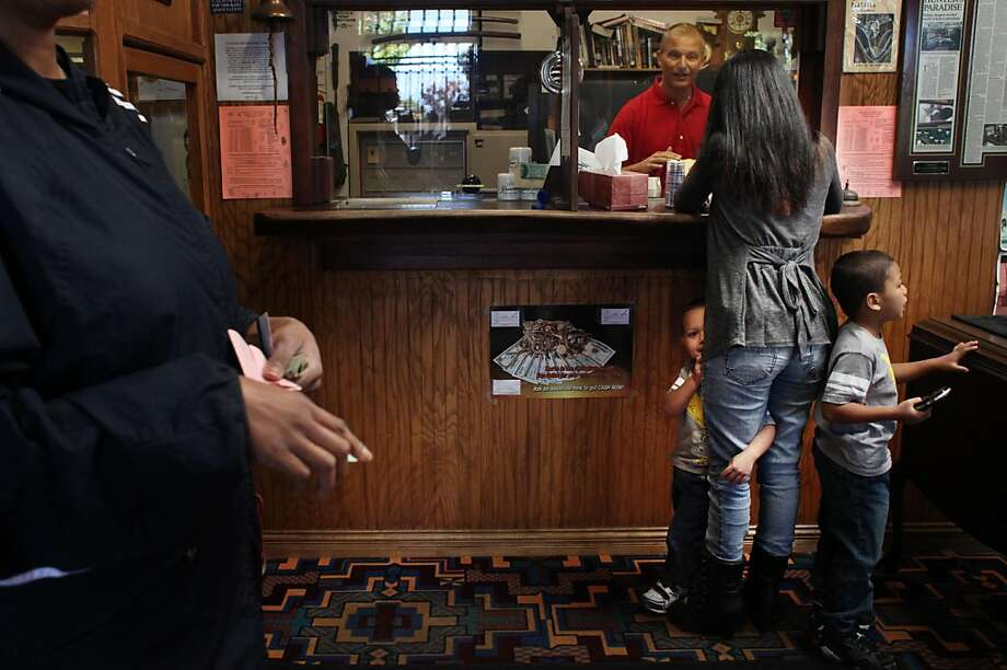 Mariano Ponce (left), 3, and Jerome Ponce (right), 5, stand with their mother, Belinda Lopez (center) of Pinole, as she pays Vito Wise (background), manager to collect her jewelery which she had pawned earlier at Granters Jewelery & Loan on Tuesday, August 2, 2011 in El Cerrito, Calif. Photo: Lea Suzuki, The Chronicle