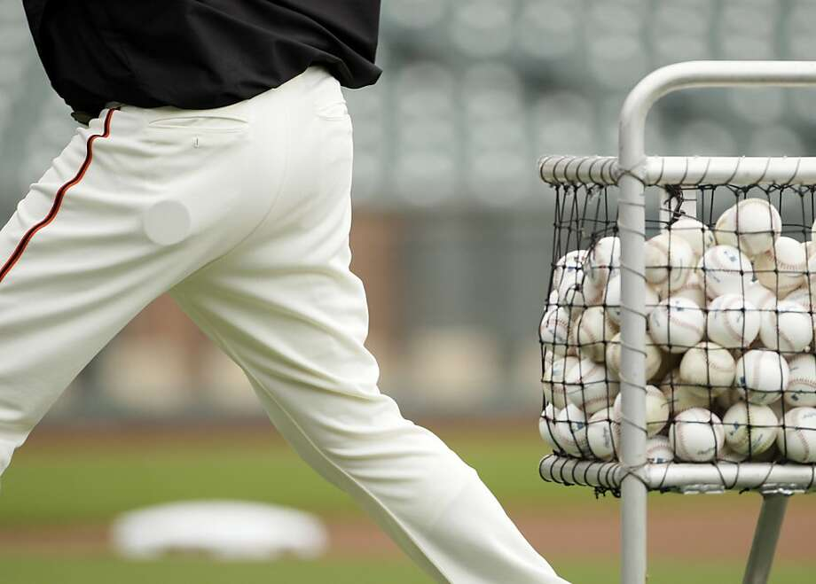 "This photo made Aug. 7, 2011, shows a tin of non-tobacco dip in the pocket of San Francisco Giants bullpen catcher Bill Hayes as he throws batting practice before a baseball game against the Philadelphia Phillies,  in San Francisco. . Ask Giants manager Bruce Bochy if he has a dip and San Francisco's skipper offers up a standard response: ""I don't do that anymore."" Hayes answers the exact same way. They learned to take that approach from hypnotherapist Dr. AlVera Paxson, who is developing quite the reputation for helping the reigning World Series champion Giants kick some nasty, decades-old habits. (AP Photo/Eric Risberg) Photo: Eric Risberg, AP"