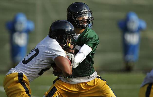 Quarterback, Zach Maynard, (15) hands to runnng back Isi Sofele, (20) during practice, as the UC Berkeley Golden Bears football team opens their fall training camp in Berkeley, Ca. on Saturday August 6, 2011. Photo: Michael Macor, The Chronicle