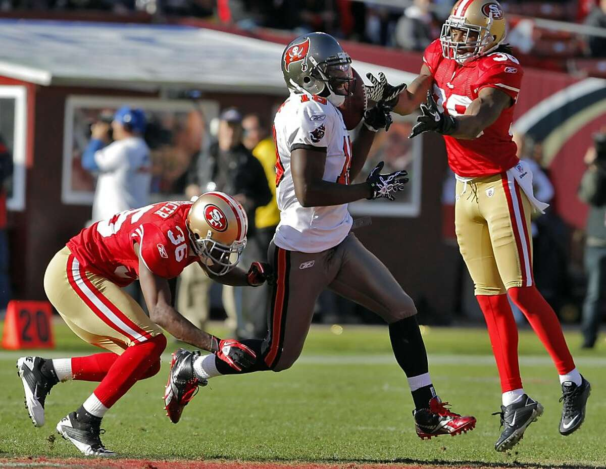 Shantae Spencer, bottom, and Dashon Goldson, top, break up a pass intended for Tampa Bay's Mike Williams in the second quarter at Candlestick Park in San Francisco on Sunday.