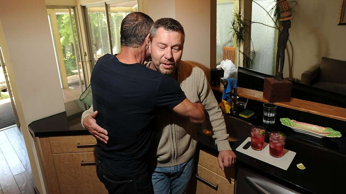 Anthony Makk, right, gets a hug from husband Bradford Wells on Monday, Aug. 8, 2011, at their San Francisco home. Though legally married in 2004, Makk faces deportation back to his native Australia.