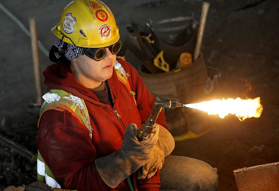 Vonie Bower adjusts her torch for cutting some steel. Vonnie Bower is a pile driver welder working beneath highway 880 in Oakland, Calif., cutting steel for the widening project. Photo: Brant Ward, The Chronicle
