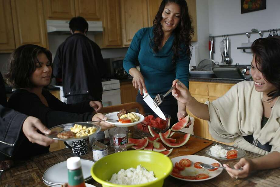 Fatemah Nikchehi cuts watermelon for her siblings as they gather around the table for a family breakfast in San Francisco Calif.,  on August 4, 2011. Photo: Audrey Whitmeyer-Weathers, The Chronicle