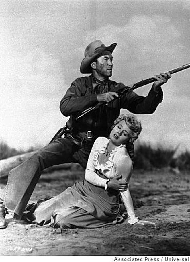 """Jimmy Stewart raises his rifle in defense of Shelley Winters in a scene from the 1950 film """"Winchester '73"""". Photo: Universal, Associated Press"""