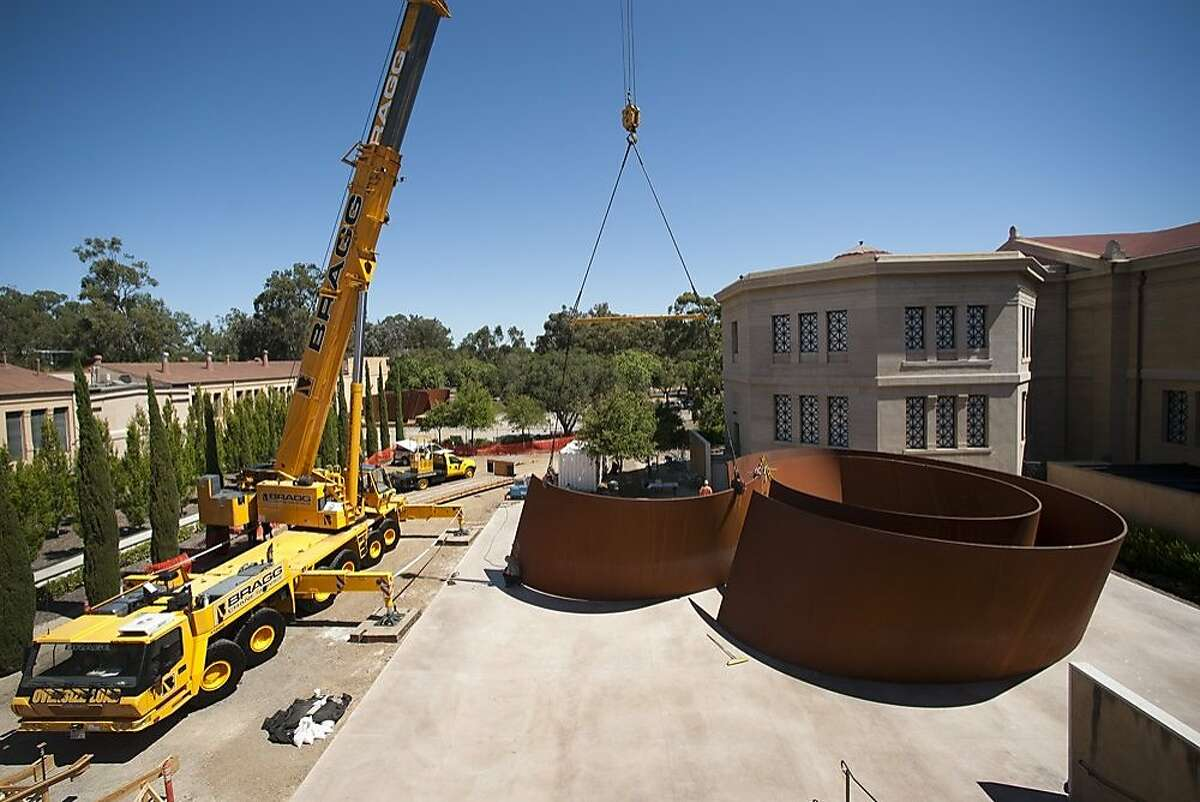 Riggers use a giant crane to assemble Richard Serra's 2006 weathering steel sculpture