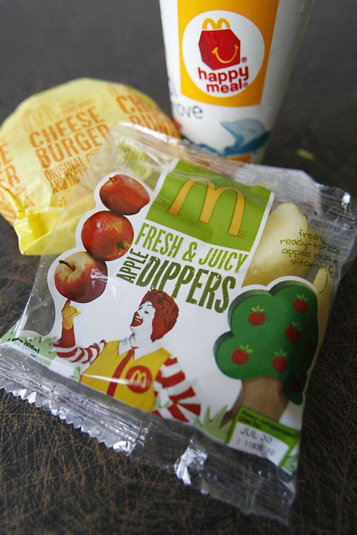 A McDonald's Cheeseburger Happy Meal with the new apple slices option is shown on Tuesday, July 26, 2011, in Pittsburgh. McDonald's Corp. says it is adding apple slices to every Happy Meal, part of the chain's larger push to paint itself as a healthy place to eat.
